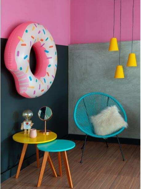 Sala colorida com cadeira azul clara e móveis amarelo e rosa
