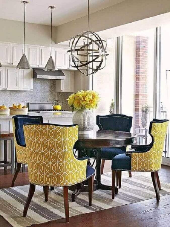 sala de jantar decorada com cadeiras clássicas coloridas e vaso de flor para mesa de jantar Foto Revista VD