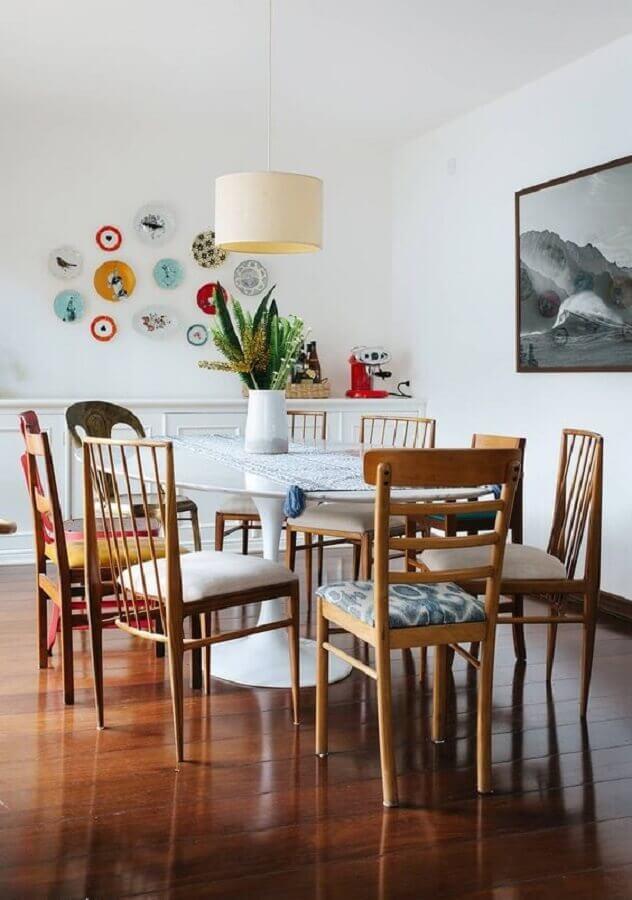 sala de jantar decorada com cadeiras de madeira e vaso para mesa de jantar redonda branca Foto Histórias de Casa