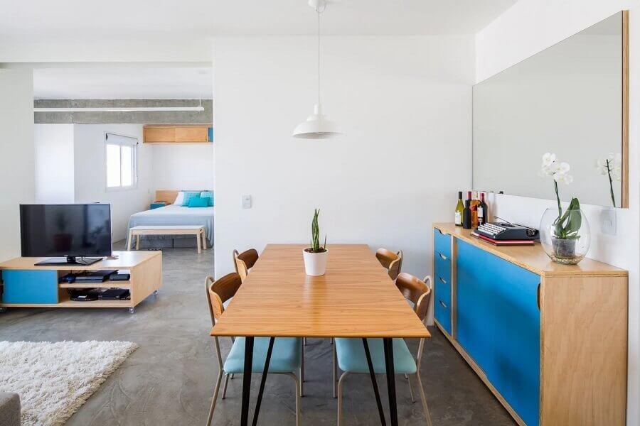 sala de jantar simples decorada com móveis de madeira e detalhes em azul e vaso para mesa de jantar Foto Marco Zero Estúdio