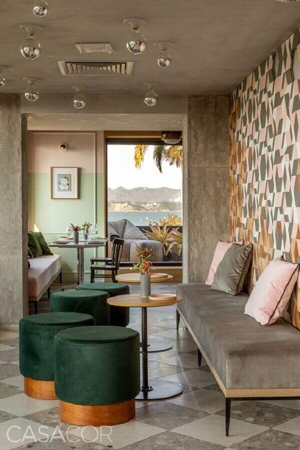 sala decorada com cimento queimado e puffs verde esmeralda Foto Casacor