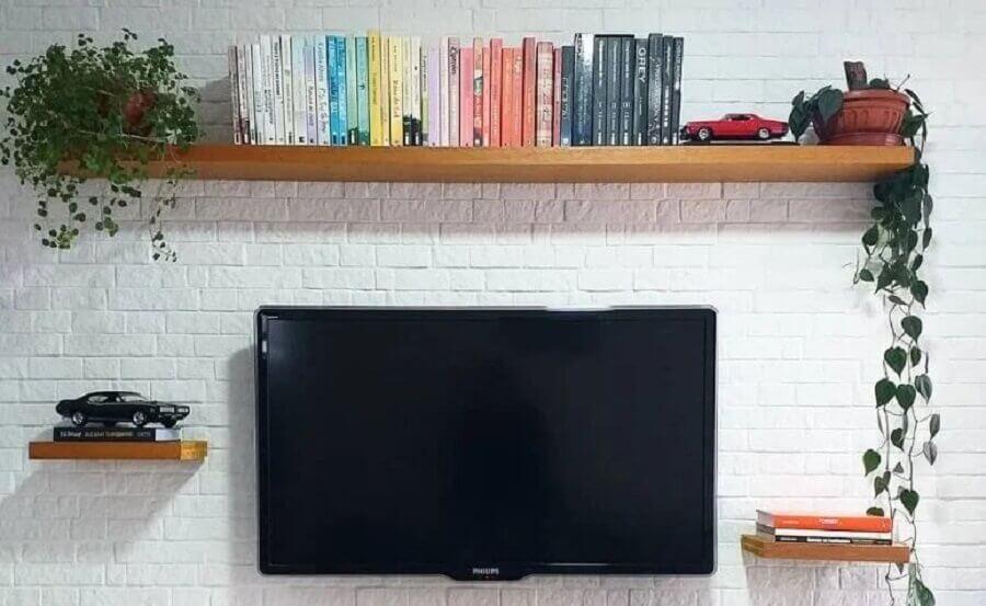 sala decorada com parede de tijolinho branca e prateleira suspensa para livros Foto Nossa Casa 93