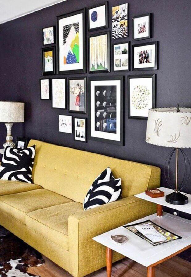 sala decorada com sofá amarelo e composição de quadros na parede preta Foto Simples Decoração