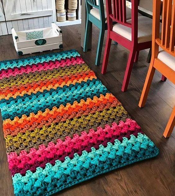 Tapete artesanal colorido combinando com as cadeiras