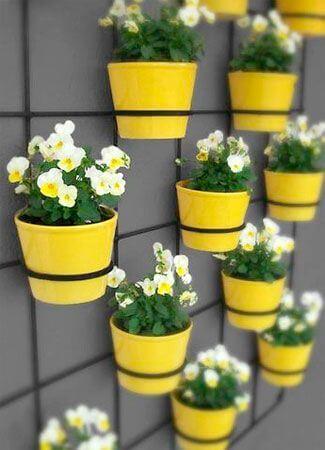 Vaso de parede amarelo com margaridas