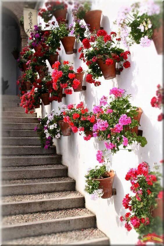 Vaso de parede com flores na escada