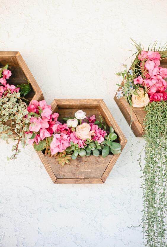 Vaso de parede de madeira com flores cor de rosa