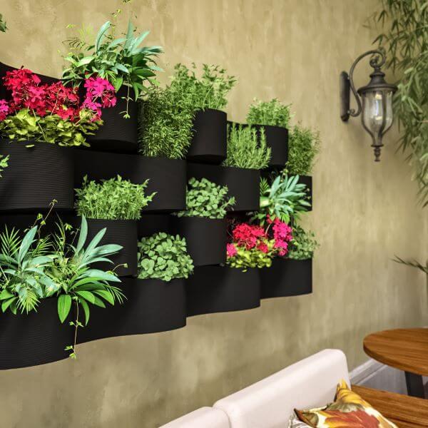 Vaso de parede preto com plantas variadas no jardim moderno
