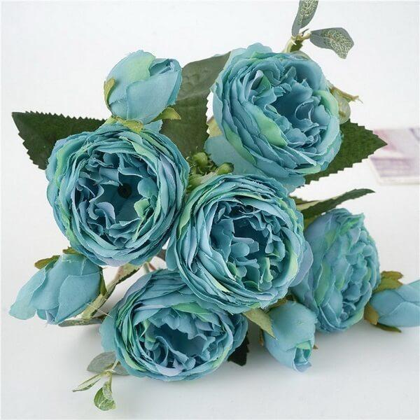 A Peônia azul artificial se destaca sobre a mesa branca