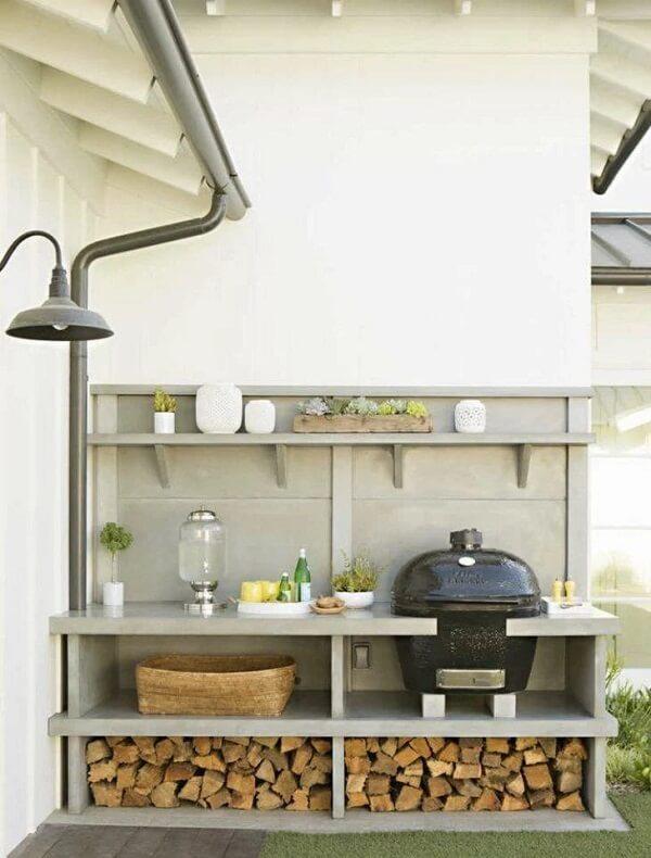 A churrasqueira portátil à carvão foi posicionada no terraço