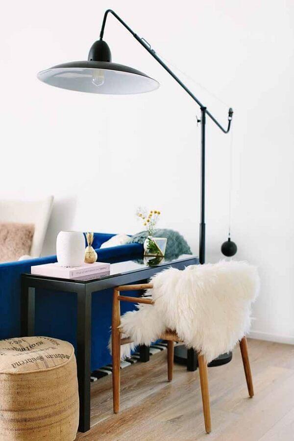 A escrivaninha foi instalada na sala e junto dela uma luminária auxilia na iluminação do espaço