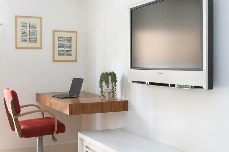 A escrivaninha suspensa de madeira fica muito discreta no ambiente