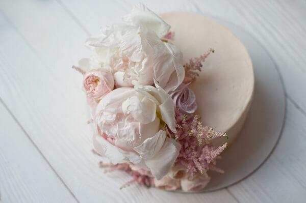 A flor de Peônia decora o topo do bolo de forma delicada e criativa