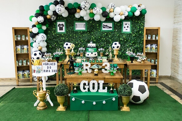 Synthetic grass on the floor and wooden furniture bring style to football theme birthday party