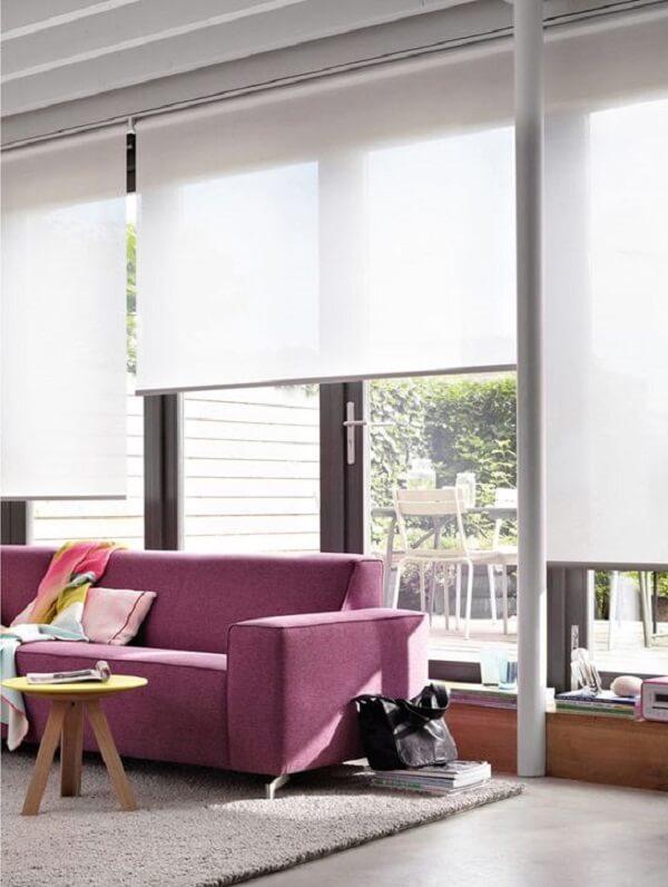 A persiana branca traz neutralidade para a sala com sofá rosa