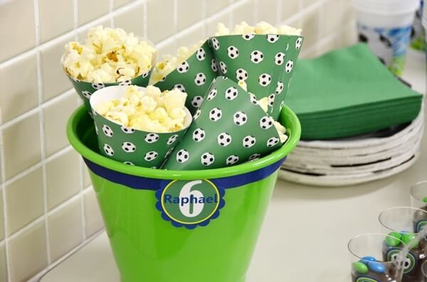 Bucket of popcorn complements simple football theme party decoration