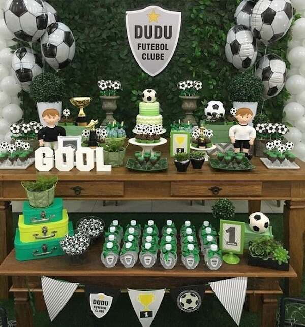 Distribua os docinhos da festa tema futebol por toda a mesa do bolo