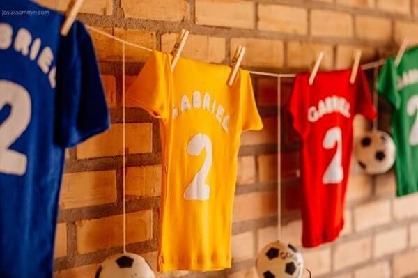 Para festa tema futebol procure fixar na parede camisetas personalizadas