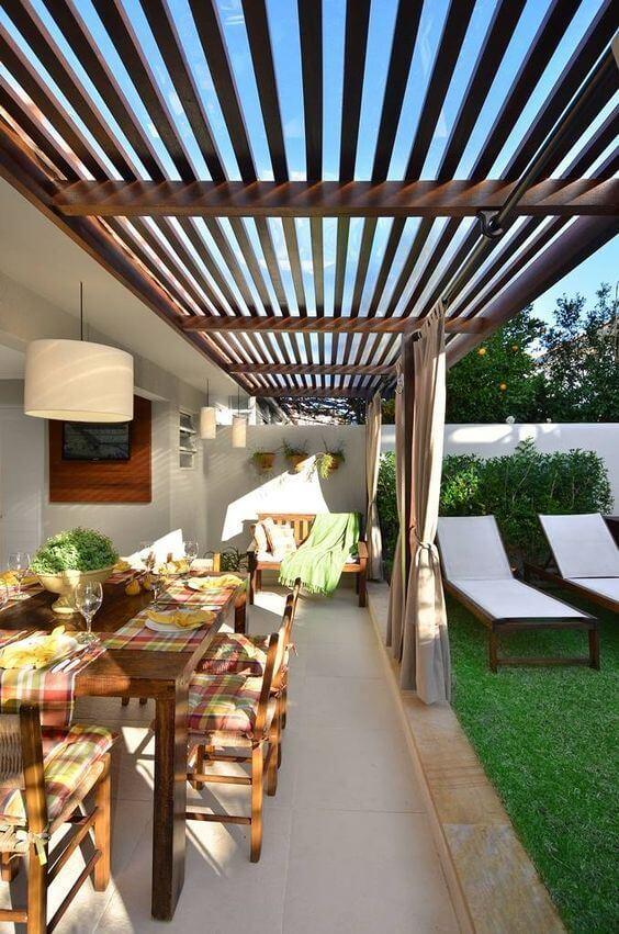Área gourmet com piscina bem decorada e espreguiçadeiras confortáveis