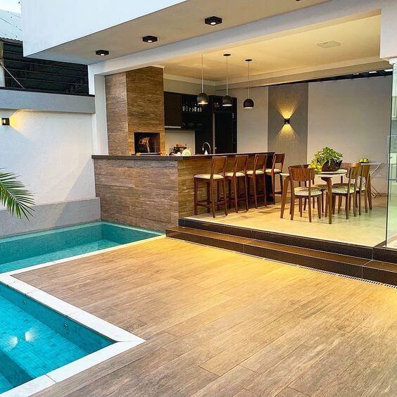 Área gourmet com piscina moderna e mesa de jantar de madeira