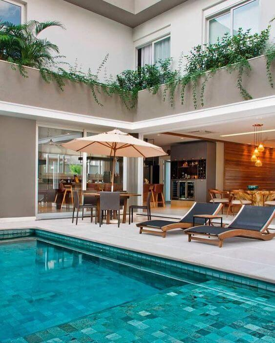 Área gourmet com piscina grande e espreguiçadeira