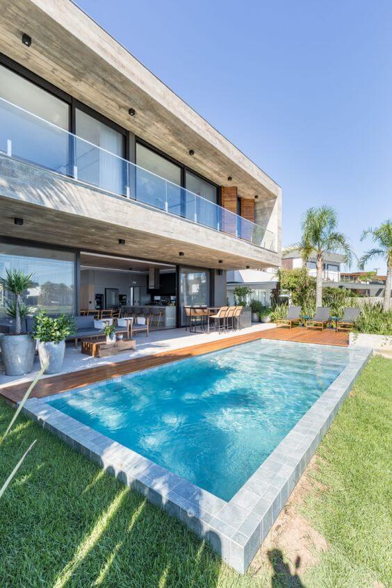 Área gourmet com piscina grande e decoração moderna
