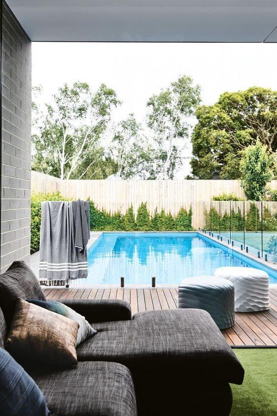 Área gourmet com piscina e sofá confortável