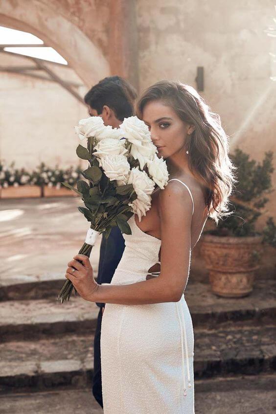 Noiva com buquê de rosas brancas