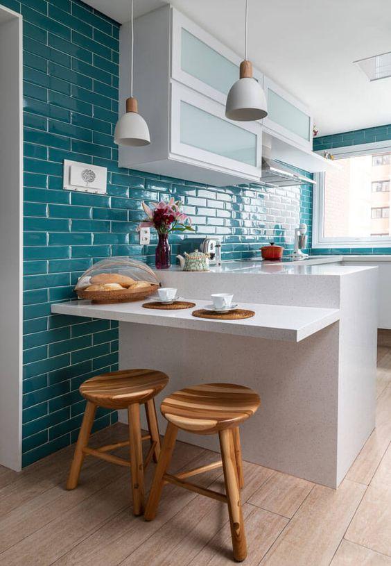 Cozinha com revestimento azul e móveis brancos