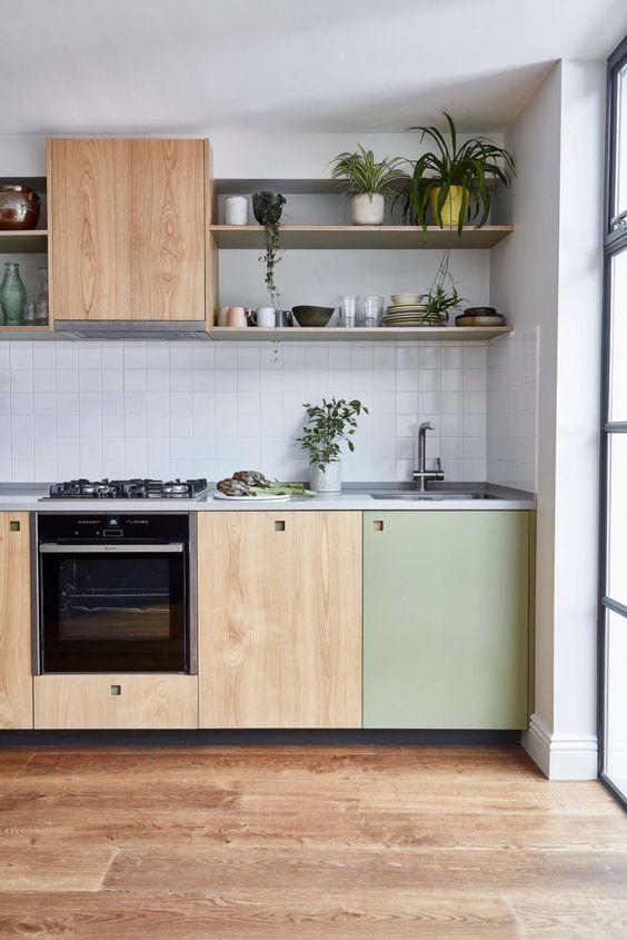 Cozinha pequena de madeira com portas verdes e prateleiras