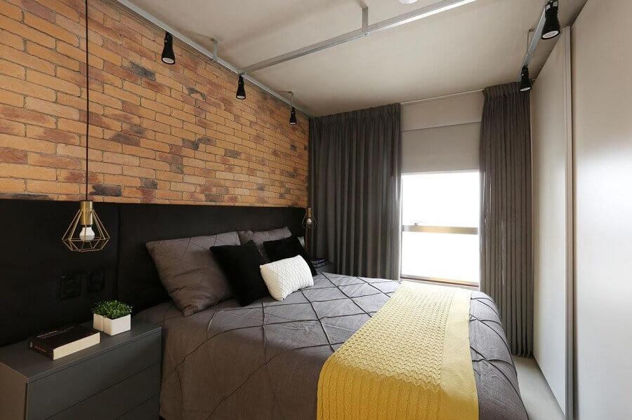 decoração com almofadas para cama em quarto com parede de tijolinho e cabeceira preta estofada Foto SP Estudio