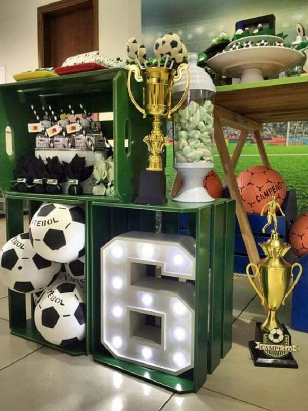 Use caixotes de madeira, letras decorativas, bolas e troféu para decorar sua mesa de bolo