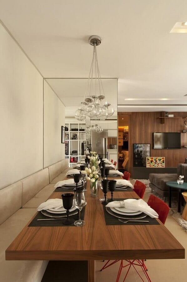 lustre para mesa de jantar decorada com banco estofado e cadeiras vermelhas Foto Pinterest
