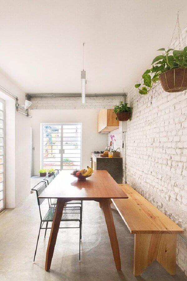 mesa com banco de madeira para sala de jantar com parede de tijolinho branca Foto INÁ Arquitetura