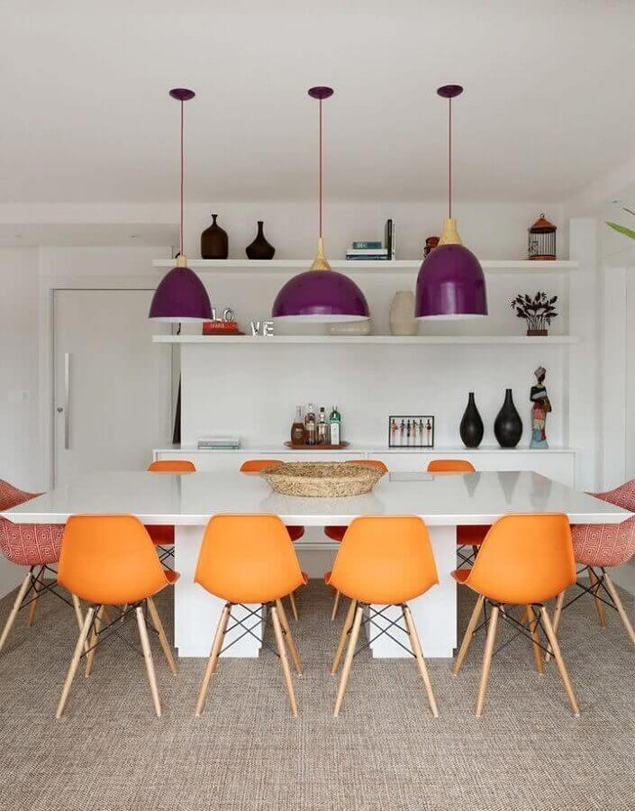 modelo roxo de lustre pendente para mesa de jantar com cadeiras laranjas Foto Apartment Therapy