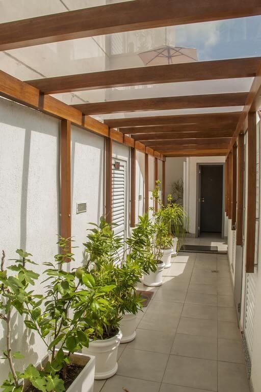 Pergolado de vidro e madeira no corredor