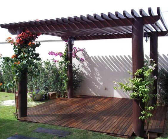 Pergolado de vidro e madeira com flores e plantas