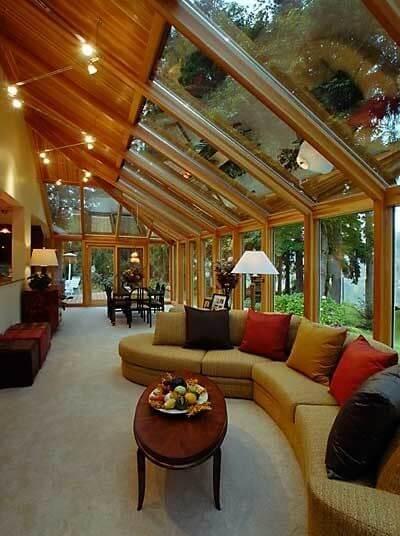 Pergolado de vidro com móveis confortáveis