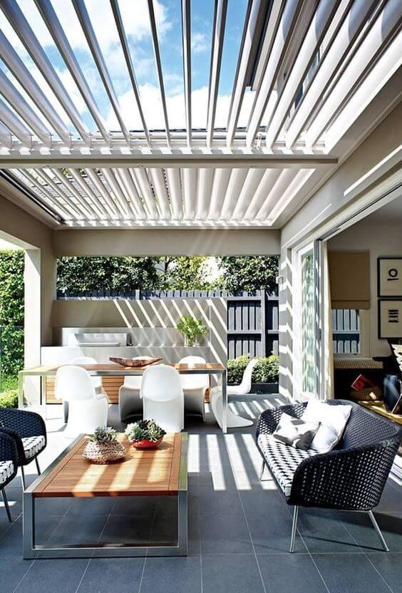 Casa com pergolado de vidro na área gourmet
