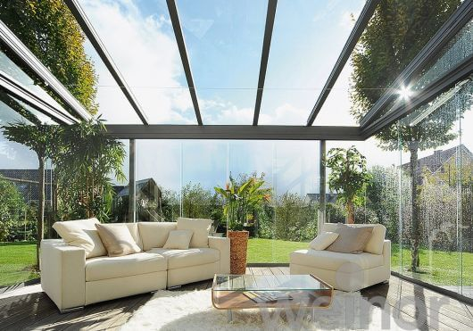 Pergolado de vidro com sofá confortável no jardim