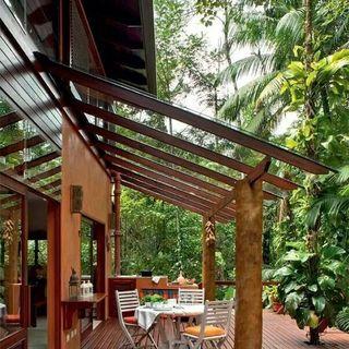Pergolado de vidro na casa de madeira