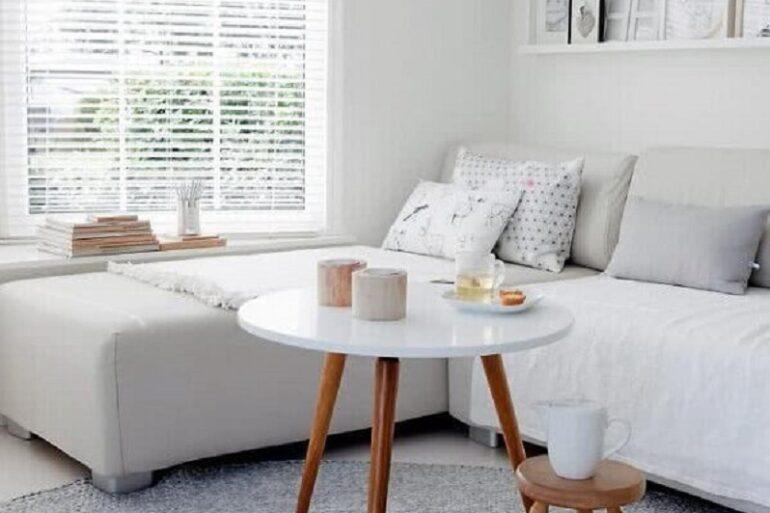 sala branca decorada com tapete de crochê cinza e mesa de centro redonad para sala Foto Archzine