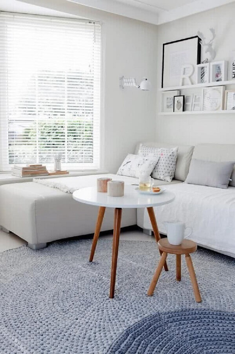 sala branca decorada com tapete de crochê cinza e mesa de centro redonda para sala Foto Archzine