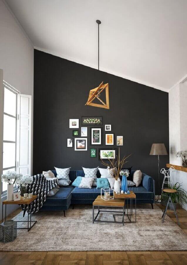 sala com parede preta decorada com sofá azul de canto e várias almofadas Foto Behance