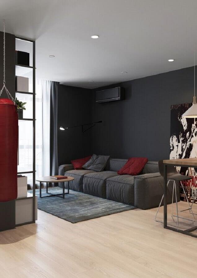 sala com parede preta decorada com sofá cinza e almofadas vermelhas Foto Pinterest