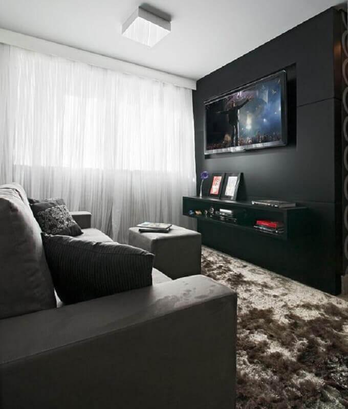sala com parede preta decorada com tapete felpudo e sofá cinza Foto Pinterest
