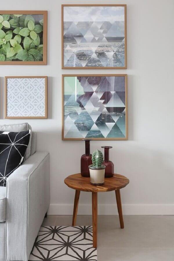 sala decorada com vários quadros e mesa de canto pequena de madeira Foto Pinterest