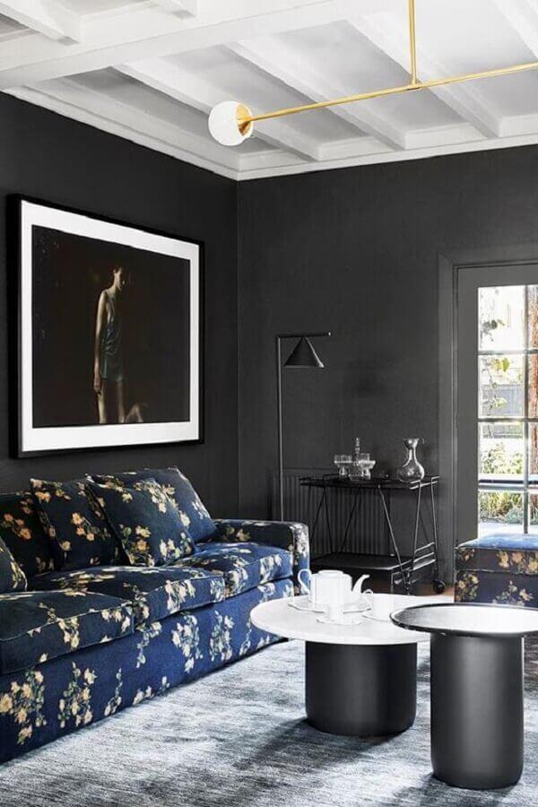 sala preta decorada com tapete cinza e sofá azul com estampa floral Foto Archzine