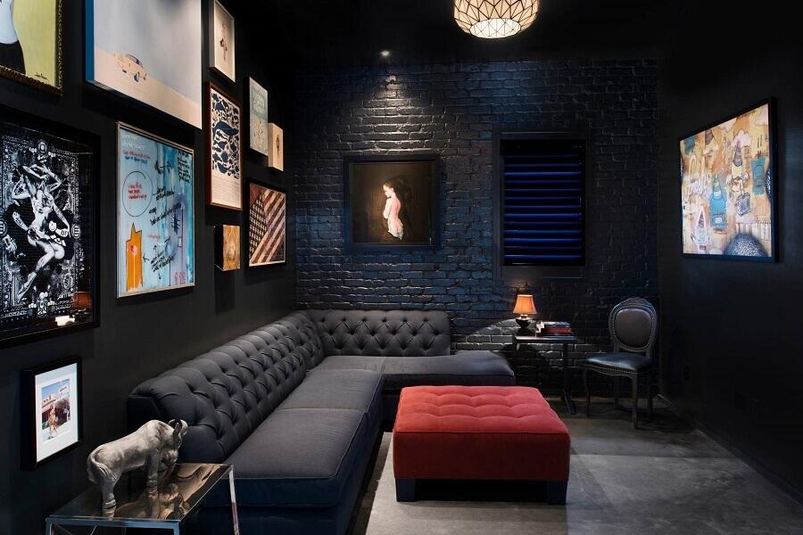 sala preta decorada com vários quadros e sofá de canto com acabamento capitonê Foto Houzz