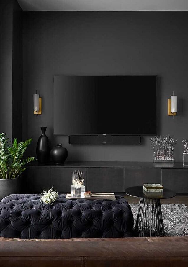 sala preta moderna decorada com puff capitonê como mesa de centro Foto Futurist Architecture